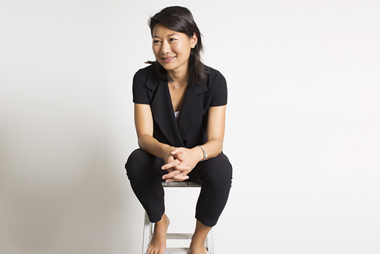 Portrait of Daisy Tam seating on a stool